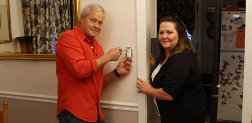 Danny Lipford installing dimmer switch with homeowner Mary Green.