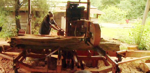 Roy Hyde sawing cedar logs on his portable, bandsaw sawmill.