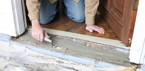 Filling rotten doorsill with concrete.