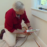Danny Lipford caulking cracks in walls.
