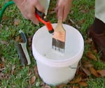 Using garden hose to clean paintbrush.