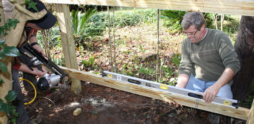 Attaching rails to a wood fence.