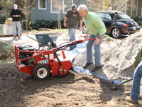 Danny Lipford tilling up ground for paver driveway.