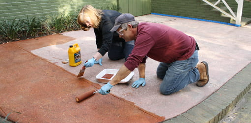 Allen Lyle and homeowner Brenda Martens staining concrete patio.