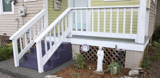 Porch with purple steps and white railings.