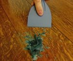 Using plastic putty knife to scrape candle wax off table.