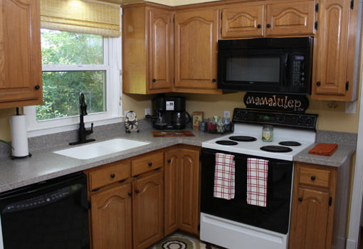 Kitchen after makeover with new countertops, sink, and faucet.