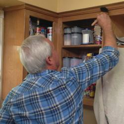 Applying polyurethane to cabinets.