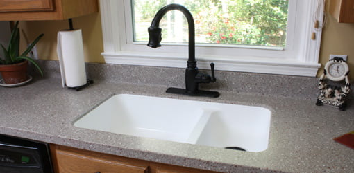 Kitchen with new solid surface countertops, sink, and faucet.