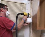 Using a sprayer to paint kitchen cabinets.