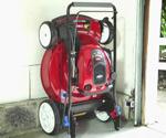 Toro SmartStow Lawn Mower stored against wall in garage.