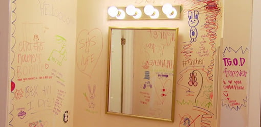 Bathroom with graffiti writing on walls.