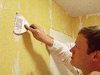 Removing wallpaper with a putty knife.