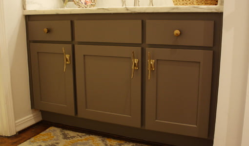 Brown painted bathroom vanity with frame and panel doors and brass cleat hardware.