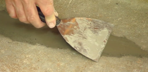 Using putty knife to smooth concrete patch in patio.