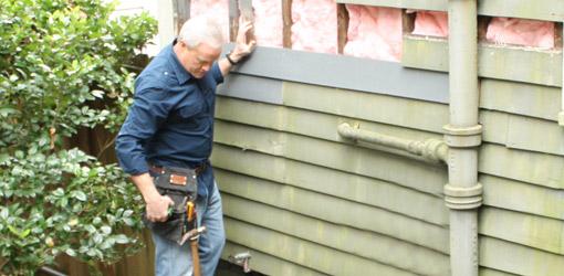 Danny Lipford replacing damaged wood siding.