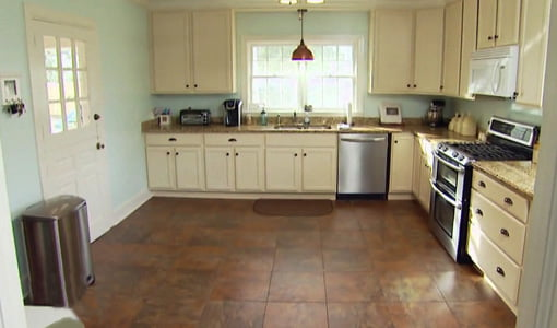 Kitchen with tile floor and white painted cabinets.
