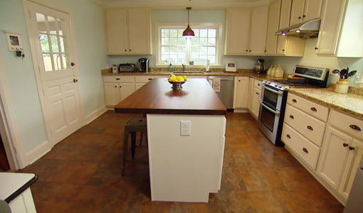 Kitchen with white painted cabinets,  tile floor, and center island with walnut wood countertop.