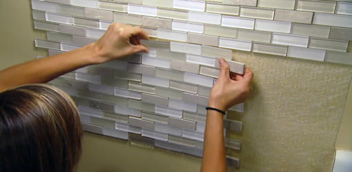 Applying glass tile backsplash to wall.