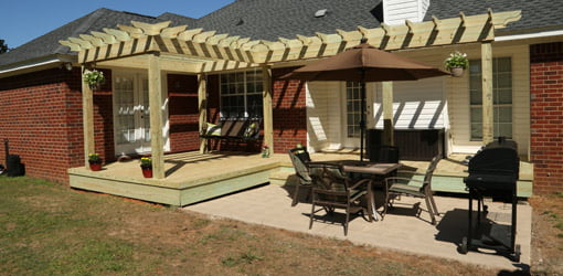 Pergola, patio, and deck on back of brick home.