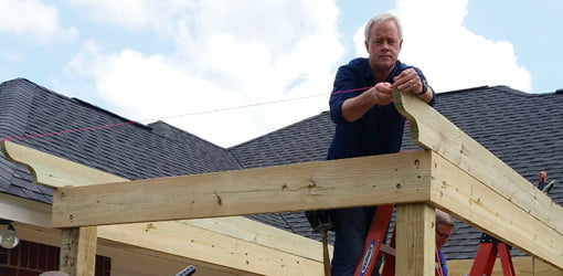 Danny Lipford on ladder installing rafters on the pergola.