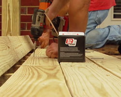 Using a cordless drill and deck screws to attaching decking.
