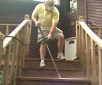 Using pressure washer to clean deck steps.