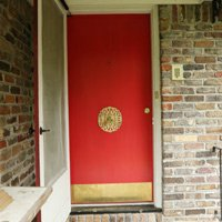 Red entry door with brass kickplate and centered doorknob.