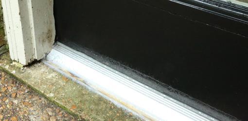 Metal threshold on black door.
