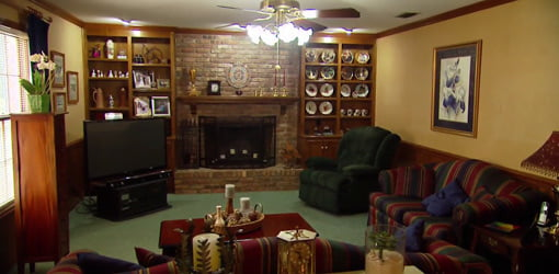 Den with brick fireplace and stained wood cabinets.
