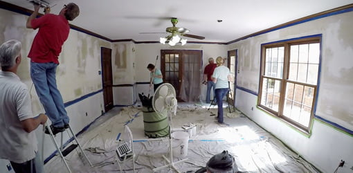 Painting and other work in room with drop cloths covering floor.
