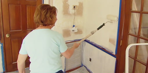 Woman painting wall with roller.