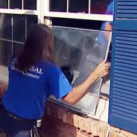 Man removing fogged window glass.