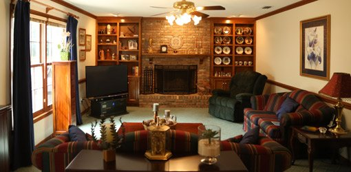 Den with brick fireplace, stained wood cabinets, and painted walls.