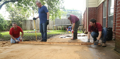 Using conduit and screed board to level patio base.