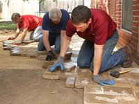 Allen Lyle, Danny Lipford, and Pavestone employee laying paver patio.