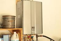 Rinnai tankless water heater mounted on wall of garage.