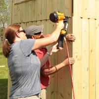 Using nail gun to install playhouse siding.