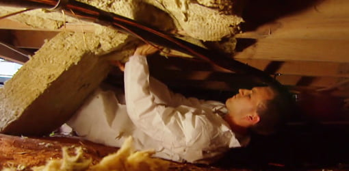 Man in white jumpsuit installing Roxul stone wool insulation in crawlspace.