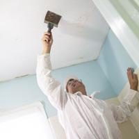 Allen Lyle scraping popcorn ceiling.