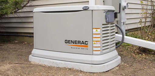 Generac Guardian standby generator in yard next to house.