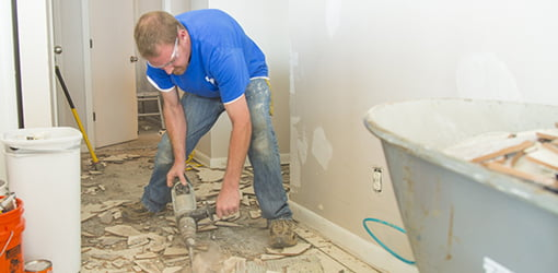 A chipping hammer is used to demolish the ceramic tile.