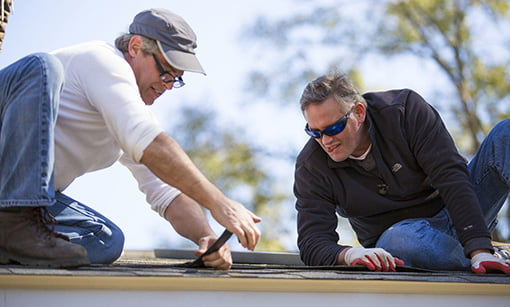 Allen Lyle and Stuart Brink install a rain diverter on the roof.