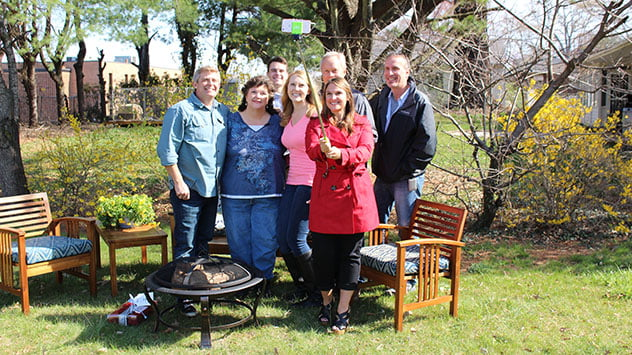 The group takes a selfie with Tamera's refinished outdoor furniture and new fire pit.