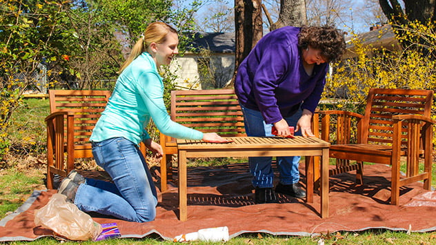 Chelsea Lipford Wolf and Tamera Pippin refinish the outdoor furniture.