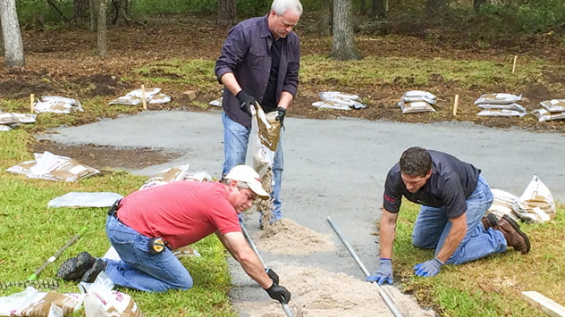 Danny Lipford, Allen Lyle and Andy Morton prepare the ground to lay the pavers.