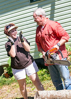 Danny Lipford shows Public Relations Manager Stephanie Greenwood how to use the chainsaw.