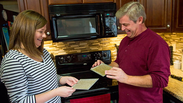 Allen Lyle shows Laura Cooper how to clean the microwave filters.