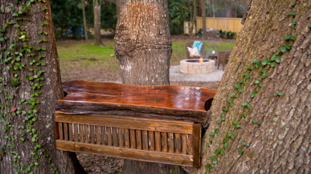 The cedar plank prep table is situated between three trees.