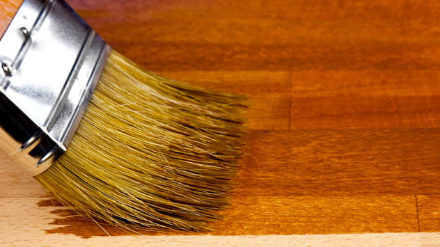 Paintbrush applying stain on a woodworking project